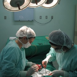 Centre AL surgical nurse assisting surgeon